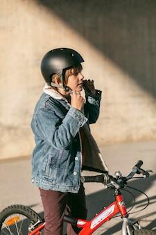 彼の自転車に乗って安全ヘルメットを持つ少年の側面図