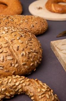 マルーンの背景にベーグルの穂軸としてパンの側面図