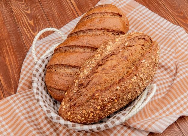 Вид сбоку хлеба в виде черного и отобранного багета в корзине на клетчатой ткани и деревянной поверхности