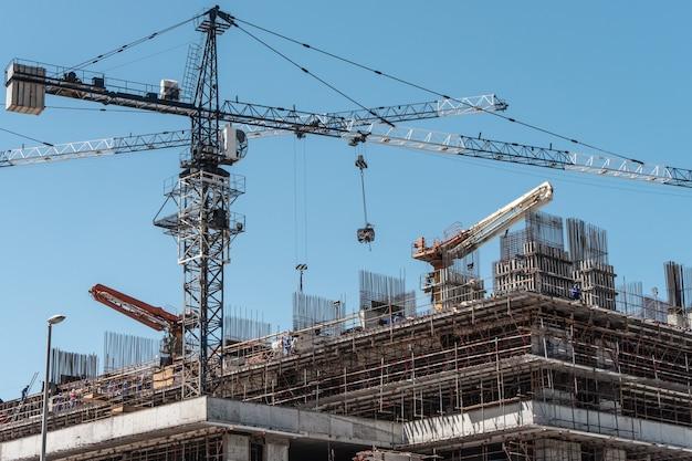 クレーンと設備を備えた建設中の建物の側面図