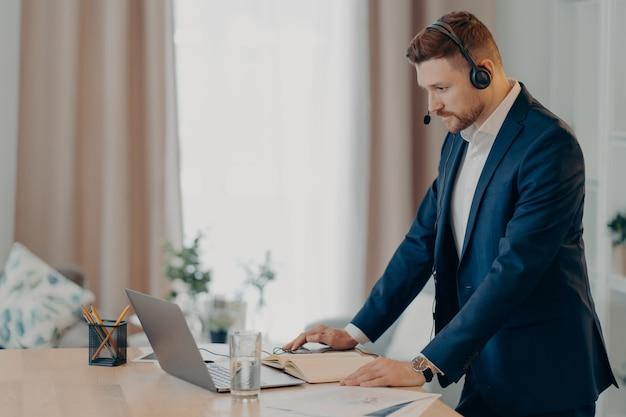 Вид сбоку бизнес-консультанта в костюме и гарнитуре, работающего на ноутбуке во время онлайн-звонка, серьезного и сосредоточенного бизнесмена, занимающегося серфингом в интернете, стоя в помещении. концепция удаленной работы