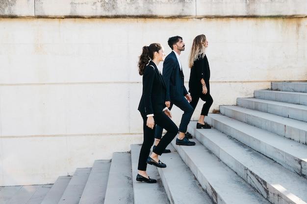 Вид сбоку деловых людей, идущих наверху