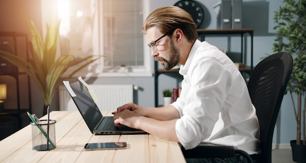 白いシャツとアイウェアのビジネスマンの側面図オフィスに座ってキーボードを入力ラップトップに取り組んでいます