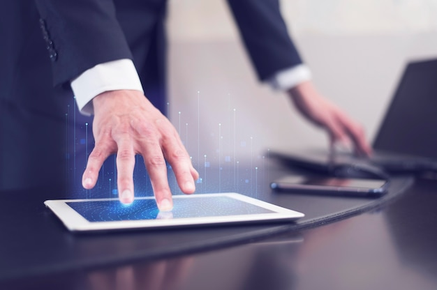 Вид сбоку бизнесмена с использованием технологии на планшете