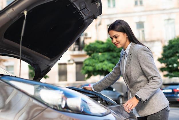Деловая женщина, проверяющая двигатель автомобиля, вид сбоку