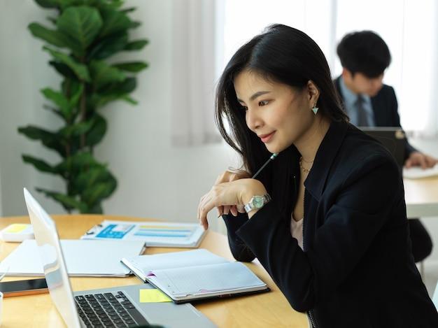 사무실 방에서 작업하는 동안 노트북에 대한 정보로 집중하는 사업가의 측면보기