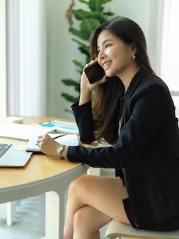 사무실 방에서 노트북 및 서류 작업을하는 동안 전화로 얘기하는 사업가의 측면보기