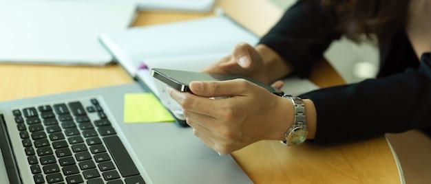 Деловая женщина с помощью смартфона, работающая с канцелярскими принадлежностями на офисном столе, вид сбоку