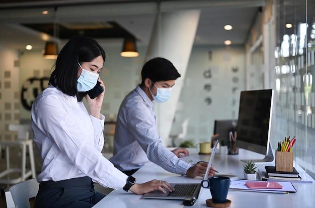 Вид сбоку деловой женщины в защитной маске, работающей на ноутбуке и разговаривающей по мобильному телефону, сидя со своим коллегой в офисе.