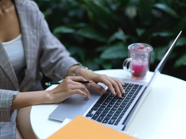 Деловая женщина, работающая с ноутбуком на журнальном столике с книгами и стаканом напитка в кафе, вид сбоку