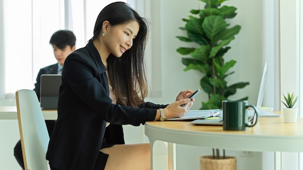 동료와 함께 사무실 방에있는 작업 공간에서 스마트 폰으로 작업하는 사업가의 측면보기