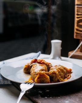 Вид сбоку голубцы с мясом рисом и овощами на тарелке