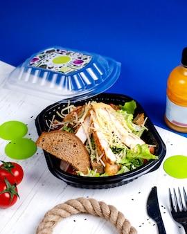 Вид сбоку салат цезарь с курицей и сыром в коробке доставки
