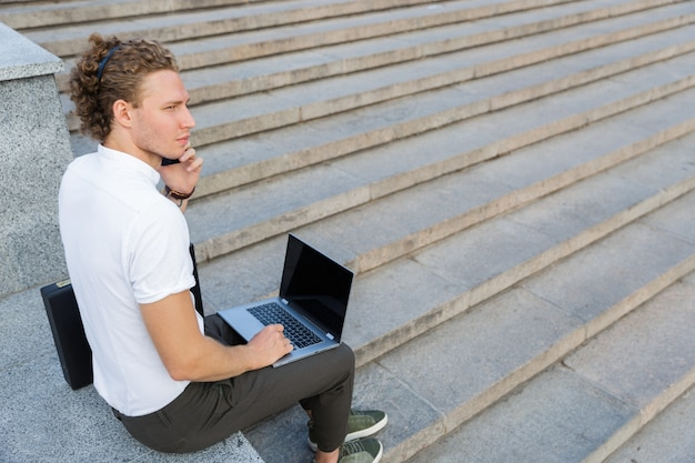 Вид сбоку спокойного кудрявого делового человека, разговаривающего по смартфону, сидя у лестницы с портативным компьютером