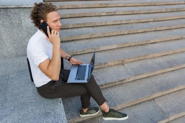 Спокойный кудрявый деловой человек с портфелем и портативным компьютером, вид сбоку, разговаривает по смартфону, сидя у лестницы