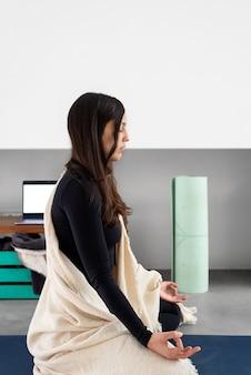 目を閉じてマインドフルネスを練習し、自宅でヨガの練習中に瞑想している穏やかな若い女性の側面図