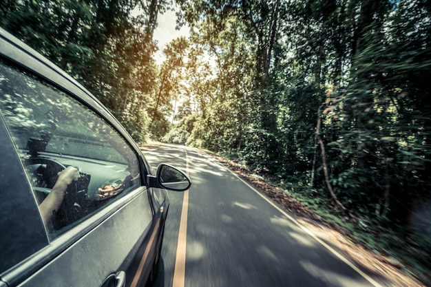 Вид сбоку вождения автомобиля по дороге в лесу шоссе