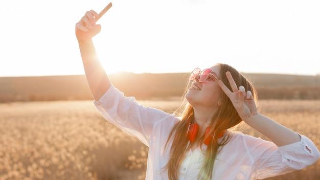 Вид сбоку беззаботной женщины с солнцезащитные очки, принимая селфи в природе