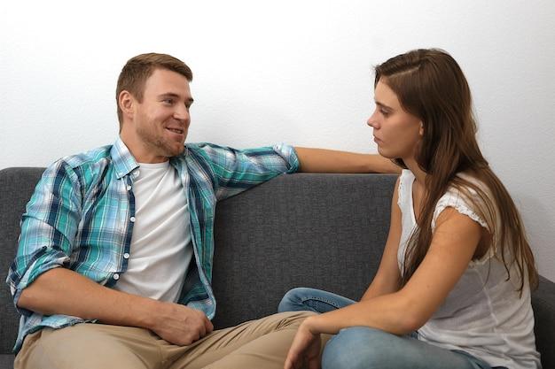 カジュアルな服装の若いヨーロッパの男性と女性の座る側面図