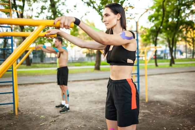 白人アスリートの側面図は、体に運動学の弾性テーピング、スポーツグラウンドでバーを使用してトレーニングしているブルネットの女性と男性とカップルしています。トレーニングの概念。