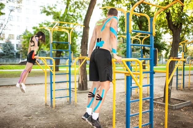 白人アスリートの側面図は、体に運動学の弾性テーピング、スポーツグラウンドでバーを使用してトレーニングしている認識できない男性とブルネットの女性とカップルします。トレーニングの概念。