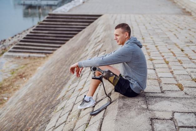 백인 장애인 운동가 스포츠웨어와 인공 다리가 부두에 앉아 강을 바라 보는 측면보기.