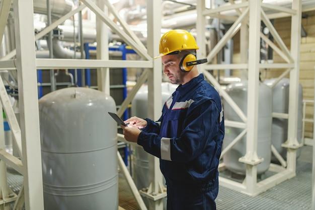 防護服、ヘルメット、重工業プラントのガスのタンクの隣に立っている間タブレットを使用してantifonesの白人労働者の側面図です。