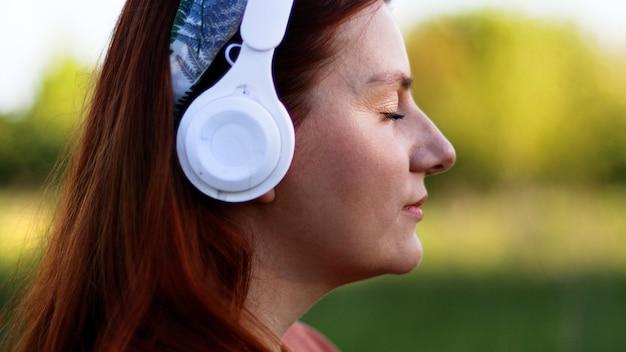 晴れた日にヘッドフォンで音楽を聴いている白人の若い女性の側面図