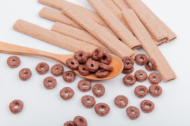 Вид сбоку зерновых в деревянной ложкой и печенье на белой поверхности