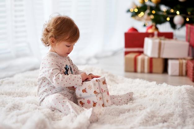 Очаровательный ребенок, открывающий рождественский подарок, вид сбоку