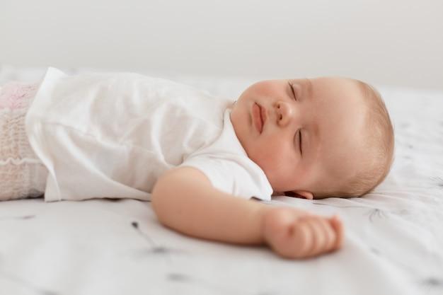 하얀 티셔츠를 입고 눈을 감고 하얀 시트에 누워 있는 매력적인 잠자는 여자 아이의 옆모습, 집에서 포즈를 취하고 평온한 어린 시절을 보냈습니다.
