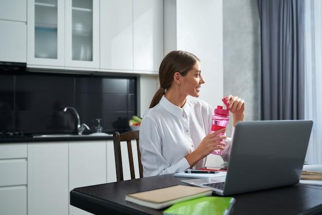 Вид сбоку очаровательной женщины, сидящей за кухонным столом с открытым ноутбуком и питьевой водой из бутылки