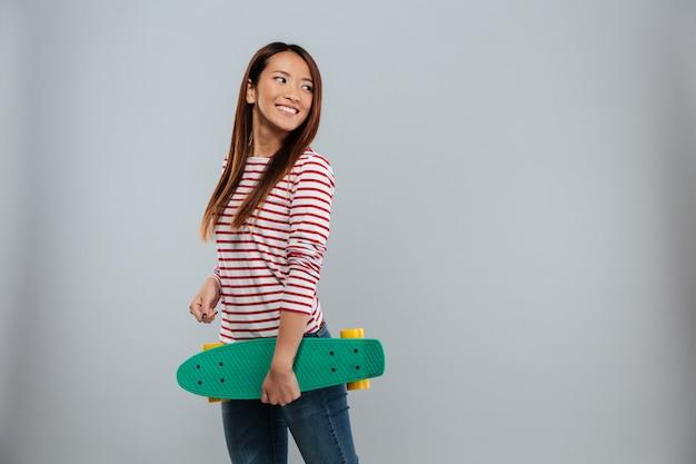 スケートボードを保持しているセーターで陽気なアジア女性の側面図