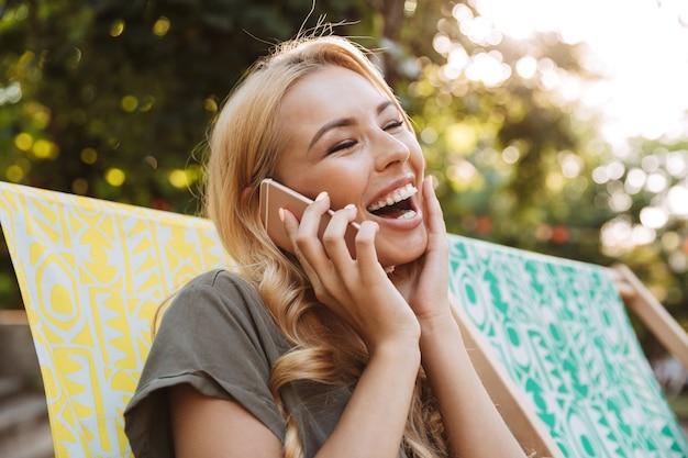 태양 안락에 앉아 야외에서 전화로 이야기 드레스에 쾌활한 금발 여자의 측면보기