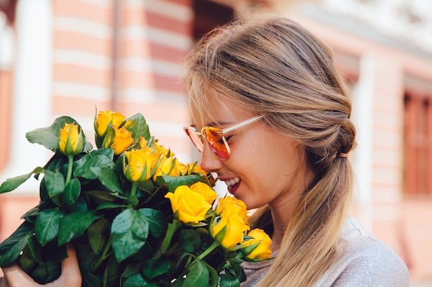Вид сбоку веселая великолепная женщина в темных очках, обнюхивает желтые розы, на улице.