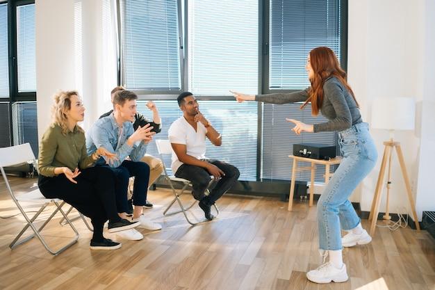 Вид сбоку веселой рыжей женщины, играющей в шарады с друзьями, показывающими пантомиму у окна в офисе. группа деятельности разнообразных разнонациональных коллег, играющих в активные игры во время тимбилдинга.