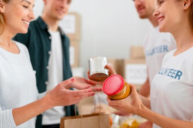 Вид сбоку на веселых добровольцев, раздающих пожертвования на еду