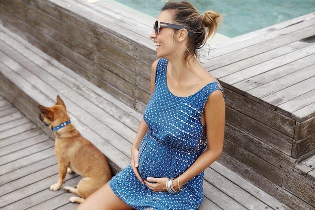 Вид сбоку веселой молодой женщины, ожидающей ребенка, сидя на скамейке возле бассейна и играя со своей собакой.