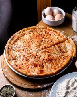 나무 테이블에 토마토와 향신료와 치즈 피자의 측면보기