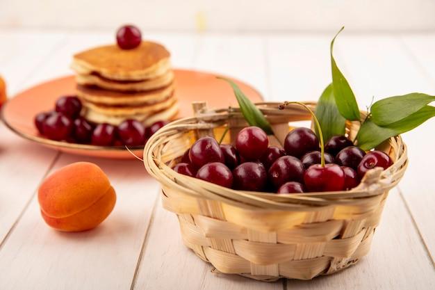 かごの中のさくらんぼとパンケーキのプレートと木製の背景にアプリコットとさくらんぼの側面図