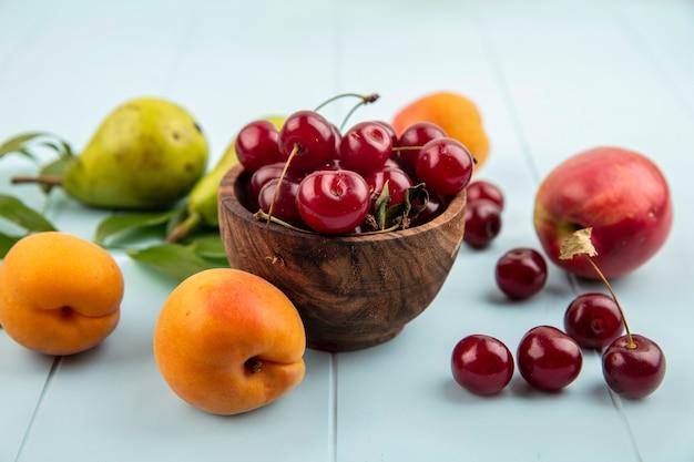 Вид сбоку вишни в миске и узор из груш, абрикосов, персиков, вишен с листьями на синем фоне