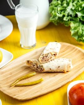 Вид сбоку куриного донера в лаваше с маринованным зеленым перцем на деревянной тарелке