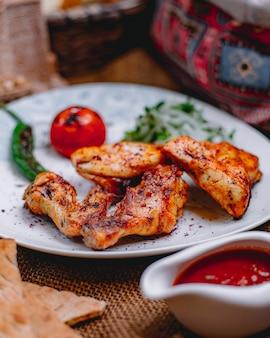 テーブルの上のチキンケバブのグリル野菜とスパイシートマトソースの側面図