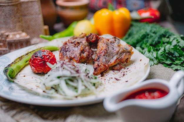 흰 접시에 양파 허브와 구운 야채와 치킨 케밥의 모습