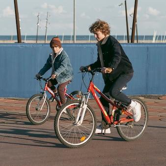 자전거에 야외에서 자식 친구의 측면보기