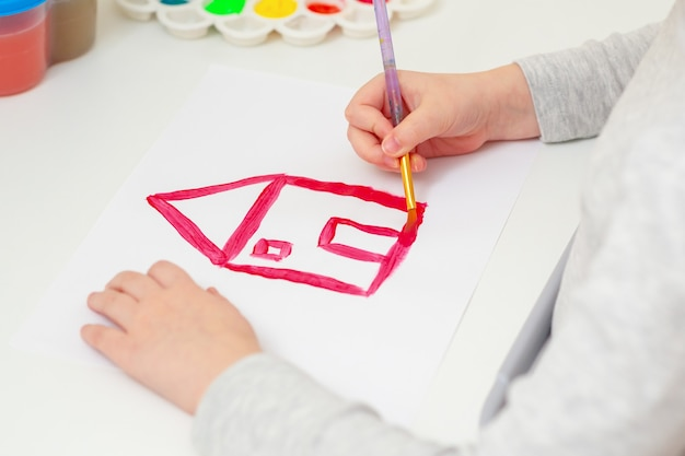 Детская рука с карандашом рисует изображение красного дома на белой бумаге, вид сбоку