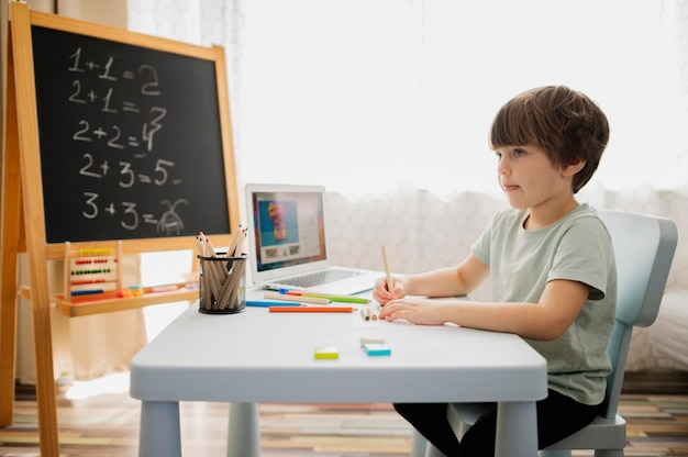 Вид сбоку ребенка, изучающего математику дома