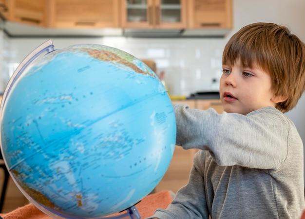 Вид сбоку ребенка, смотрящего на земной шар
