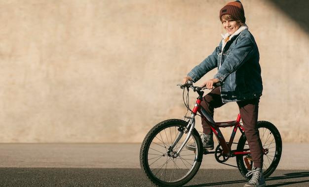 복사 공간 야외에서 자전거에 아이의 측면보기