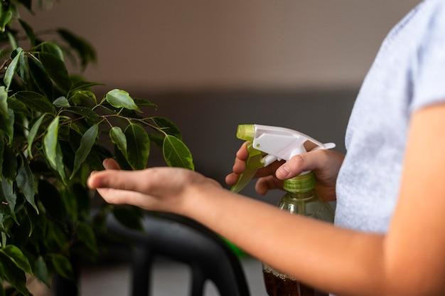 물으로 식물을 살포하는 아이의 측면보기